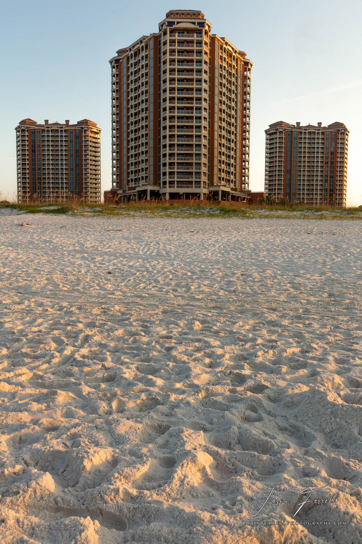 An early morning sunrise photo of the Portofino Island Resort Towers on the beach.