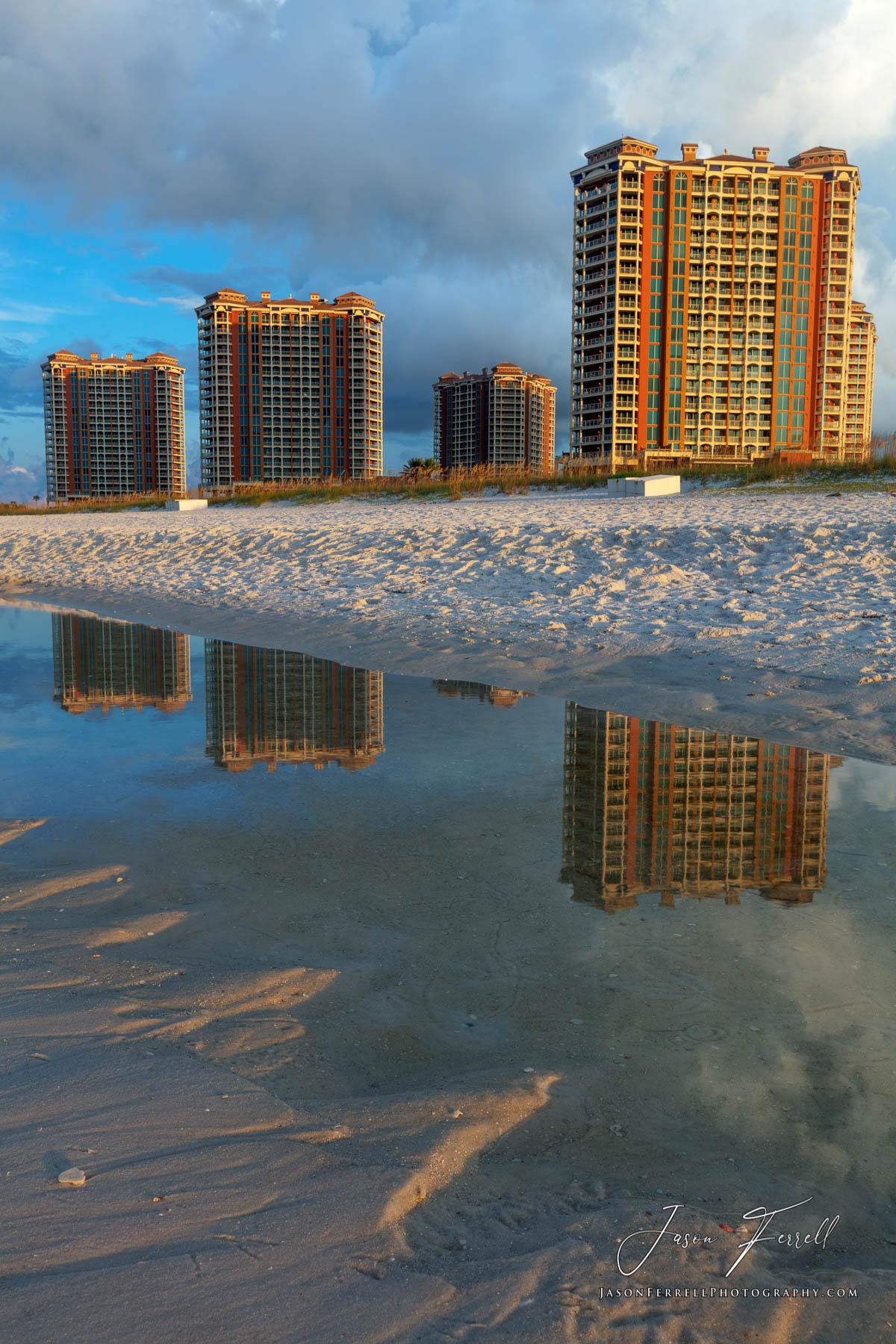 An early morning sunrise photo of the Portofino Island Resort Towers reflecting from a tidal pool on the beach.
