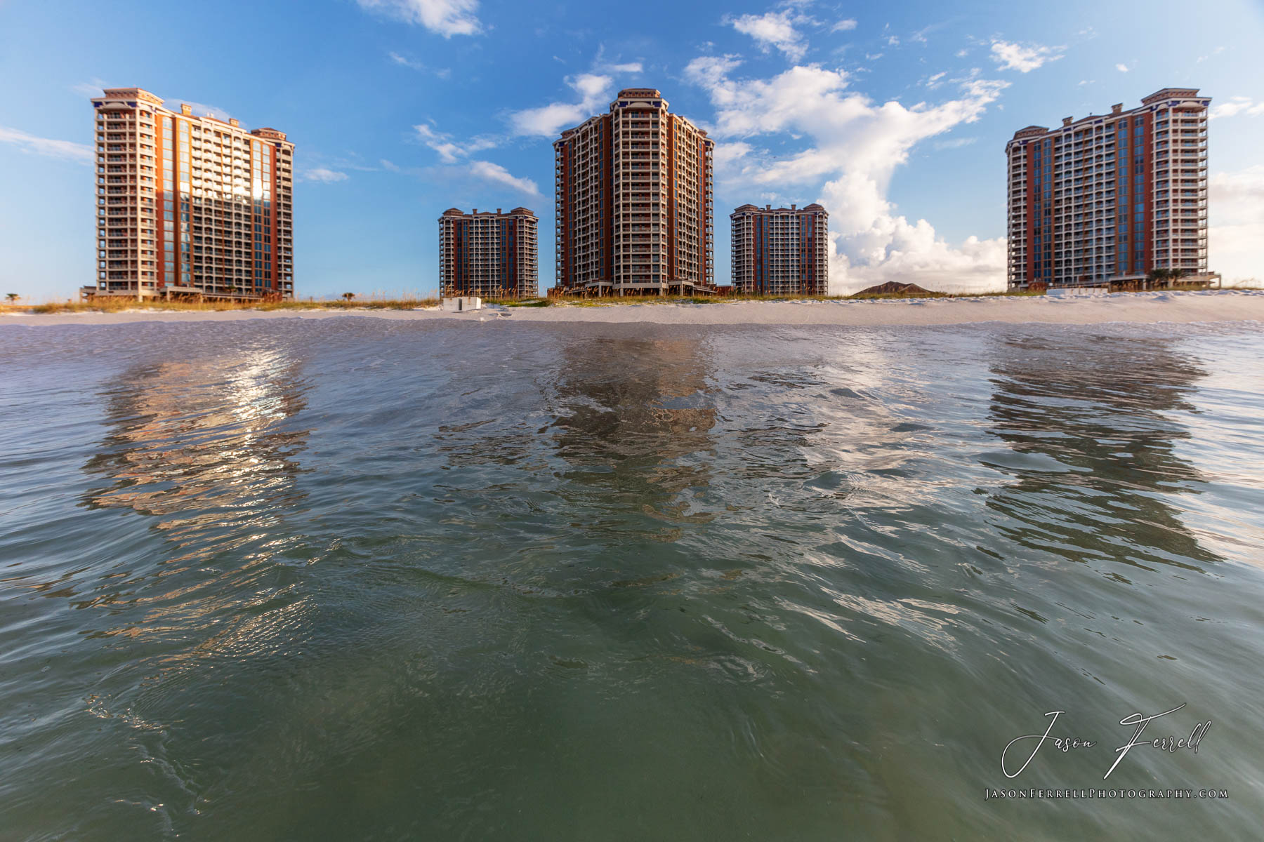 An early morning sunrise photo of the Portofino Island Resort Towers from the Gulf of Mexico.